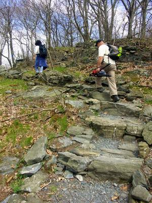 Hikers climb rock steps on the Summit Trail, in Elk Knob State Park.